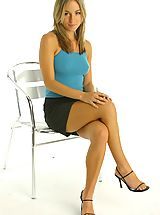 Red Heels, Melanie sitting in a chair wearing a tight blue top and a black mini skirt with white lacy underwear