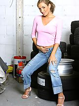 Sexy Secretary, Melanie looking beautiful posing in a car workshop next to a stack of tyres wearing a tight pink top with denim jeans and blue lingerie.