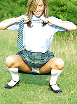 Melanie takes a wander in the park wearing a college uniform consisting of tartan skirt