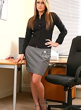 Between Legs, Candice wearing a black blouse with a grey skirt and grey stockings.